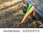 colored umbrella lying on a... | Shutterstock . vector #1225215772