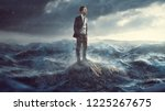 businessman standig on a rock... | Shutterstock . vector #1225267675