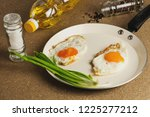 two fried eggs in metal beige...
