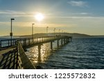 the sun shines down on the pier ... | Shutterstock . vector #1225572832
