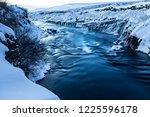 hraunfossar waterfall in winter ... | Shutterstock . vector #1225596178