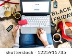 Body part of woman female adult with red high heels buying making payment on fashion cloth internet online store shop by typing credit debit card details with laptop during black friday holiday. - stock photo