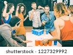 happy friends playing beer pong ...   Shutterstock . vector #1227329992