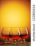 Three glasses of cognac on yellow background - stock photo