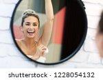 young woman using deodorant in...   Shutterstock . vector #1228054132