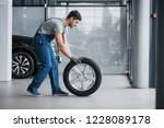 mechanic holding a tire tire at ... | Shutterstock . vector #1228089178