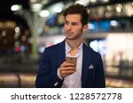 young man using his cellphone... | Shutterstock . vector #1228572778