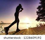 runner  sprints along lake.... | Shutterstock . vector #1228609192