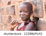 Stock photo an year old ugandan girl smiling holding a pen against her mouth and leaning against a brick 1228869142