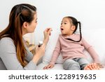 mother checking temperature of...   Shutterstock . vector #1228919635