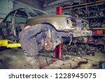 a worker repairing a car wheel | Shutterstock . vector #1228945075