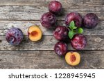 ripe plums on a rustic wooden...   Shutterstock . vector #1228945945