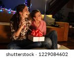 young woman opens a gift which... | Shutterstock . vector #1229084602