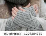 hands in woolen mitts with a... | Shutterstock . vector #1229204392