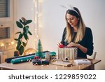 happy young woman wrapping gifts | Shutterstock . vector #1229859022