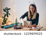 happy young woman wrapping gifts | Shutterstock . vector #1229859025