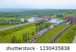 Small photo of Russia, Baikal - August 02, 2018: Trans-Siberian Railway, the coast of Lake Baikal. Movement of trains on the iron bridge across the river flowing into Baikal, From Drone