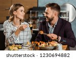 Small photo of Lovely couple amorously looking at each other and eating sushi rolls in restaurant