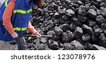 female worker breaking the coal using hammer - stock photo