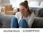 upset young female sit on couch ... | Shutterstock . vector #1230899545