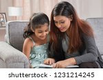 mother reading book to daughter ... | Shutterstock . vector #1231214245