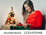 young woman opening christmas... | Shutterstock . vector #1231455448