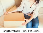 young woman opening packet at... | Shutterstock . vector #1231458328