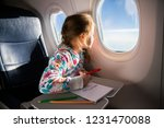 Small photo of Child drawing picture with crayons in airplane. Little girl occupied while flying in aircraft. Travel with family and kids. Blue sky and sun outside the window