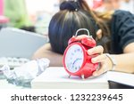 Small photo of Woman are holding a red alarm clock and books placed on the table in a languishing condition.