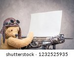 Small photo of Retro Teddy Bear toy with leather aviator's helmet hat and goggles typing on old aged classic typewriter with clean paper sheet blank front concrete wall background. Vintage style filtered photo