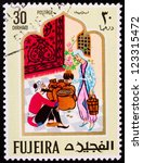 Small photo of FUJAIRAH - CIRCA 1967: A stamp printed in Fujairah shows the images of man and woman with gold from the story of Ali Baba, circa 1967.