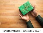 green gift box on male hand... | Shutterstock . vector #1233319462