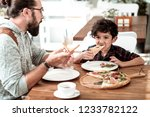 Stock photo lunch in cafeteria happy bearded father and cute funny son having lunch in cafeteria eating yummy 1233782122