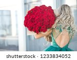Small photo of Elegant beautiful blonde woman is wearing green fashion dress in cafe holding with big bouquet of 101 red roses. Woman eating cake and drinking tea in outdoor cafe.