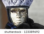 VENICE - 14 FEBRUARY: An unidentified woman disguised as a typical Venetian mask decorated with gold detailing perform at the most famous European Carnival on February 14, 2010 in Venice. - stock photo