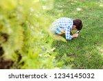 crouching school boy using... | Shutterstock . vector #1234145032