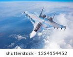 Combat fighter jet on a military mission with weapons - rockets, bombs, weapons on wings flies high in the sky above the clouds - stock photo