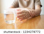 Stock photo elderly woman hands w tremor symptom reaching out for a glass of water on wood table cause of 1234278772