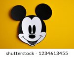 Small photo of RUSSIA, ST.PETERSBURG - NOVEMBER 19, 2018: Black and white face of Mickey Mouse out of paper on a yellow background.