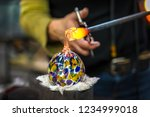a glass blower shaping molten... | Shutterstock . vector #1234999018