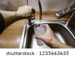 a man pours a glass of water... | Shutterstock . vector #1235663635