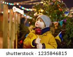 little boy eating red apple... | Shutterstock . vector #1235846815
