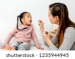 mother checking temperature of... | Shutterstock . vector #1235944945