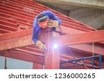 Risky welder while climbing and welding on top of the steel roof structure work at the building construction site. Skilled worker is welding on the high steel structure at the construction project. - stock photo