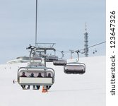 Skiers in chairlift approach the summit station at a ski resort in South Tyrol. - stock photo