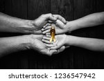 Small photo of golden ribbon childhood symbol of the fight against cancer in children in hands on a dark background. concept of helping patients with sarcoma and bladder cancer.black and white.