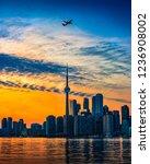 Small photo of TORONTO CITY SKYLINE AT SUNSET - Beautiful sunset scene of Toronto cityscape with airplane flying past dramatic diagonal clouds across sky. Blue and orange colors. Toronto, Ontario, Canada