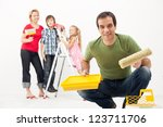 Happy family with kids redecorating their home - painting together - stock photo