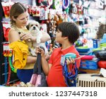 Stock photo glad tweenager boy and his smiling adult mother looking for supplies for little dog in petshop 1237447318