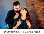 man helps his wife to wear... | Shutterstock . vector #1237817065